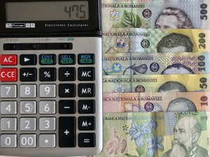 Un calculator împreună cu câteva bancnote românești